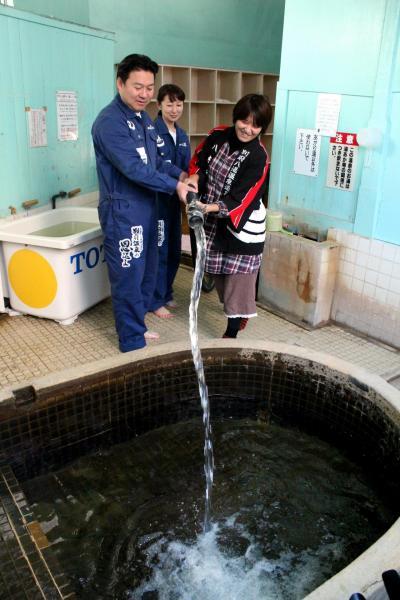 大分県別府市の寿温泉に、草津の湯を入れる長野恭紘・別府市長(左)ら=2017年11月