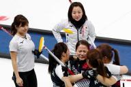 日本対韓国の対戦となったカーリング女子の準決勝で、延長の末に日本を下し、藤沢五月(中央奥)らが見つめるなか、抱き合って喜ぶ韓国チーム