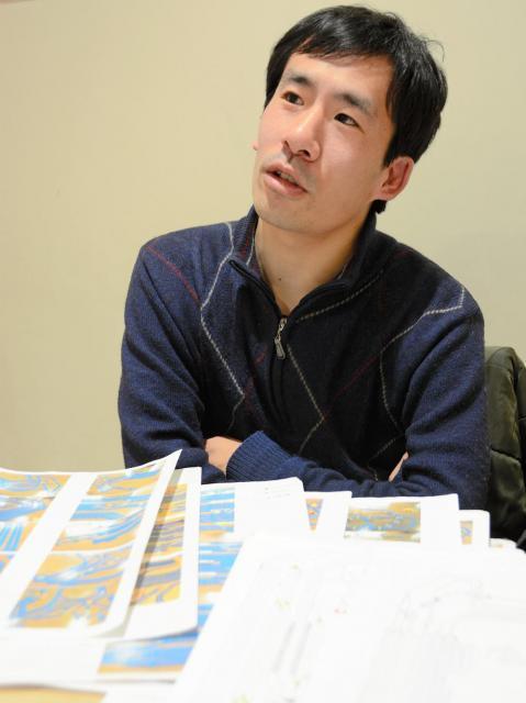 配線図や設計のマニュアルを見ながら、プラレールを語る松岡さん=さいたま市大宮区
