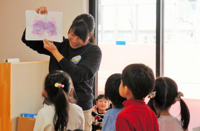 子どもが書いた絵を見せ、話す保育士(写真はイメージです)