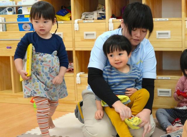 散歩前の子どもたちが靴下をはく手伝いをする保育士(写真はイメージです)