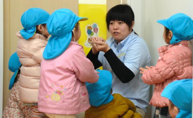 散歩に出かける前、子どもたちと手遊びをする保育士(写真はイメージです)