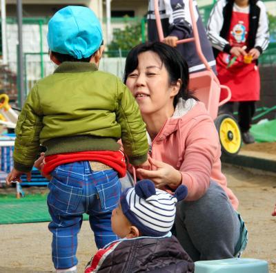 園庭で子どもたちと遊ぶ保育士(写真はイメージです)