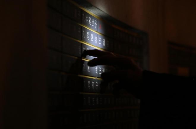 ペンライトの明かりを頼りに肉親の名前を探す=1月17日午前4時46分、神戸市中央区、細川卓撮影
