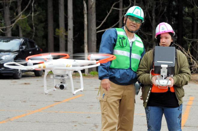 ドローンスクールの実習でドローンを操縦する高校生(右)と講師=2017年4月29日、石川県白山市