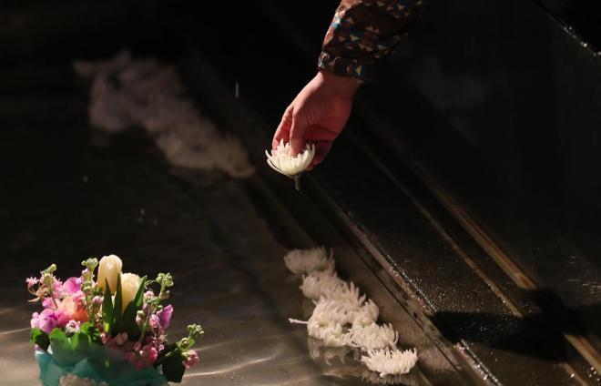 地上にある水盤に白菊を献花する人々=1月17日午前6時52分、神戸市中央区、細川卓撮影