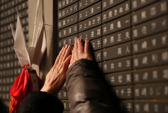 訪れた人は、亡くなった家族や友人の名前を見つけると、銘板をなで、祈りを捧げていました=1月17日午前6時16分、神戸市中央区、細川卓撮影