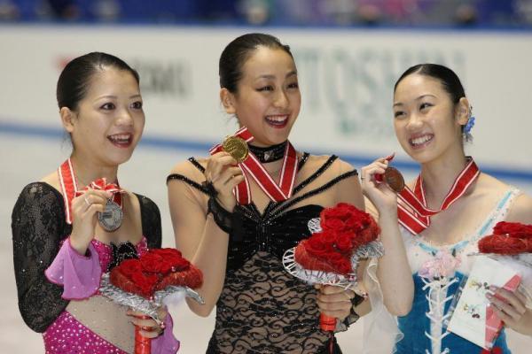 表彰式のあとメダルを掲げる、優勝の浅田真央(中央)、2位の鈴木明子(左)、3位の中野友加里=2008年11月29日