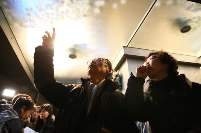 地下の瞑想空間から見上げると、ガラスの天井越しに水盤に浮かんだ献花が透けて見えます=1月17日午前7時14分、神戸市中央区、細川卓撮影