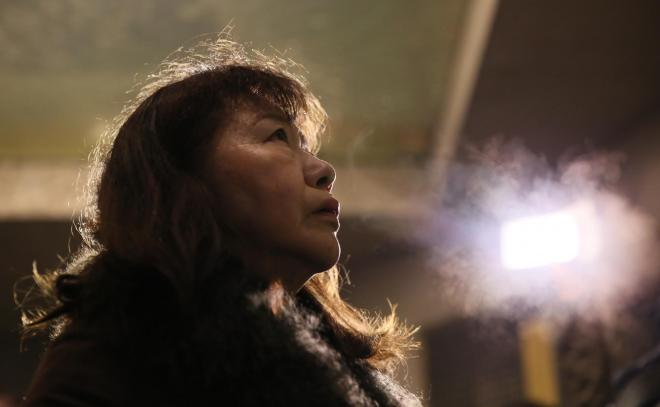白い息を吐きながら銘板を見つめる女性=1月17日午前5時7分、神戸市中央区、細川卓撮影
