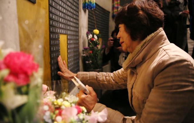 長男の名前に触れる野田貴美子さん=1月17日午前6時16分、神戸市中央区、細川卓撮影