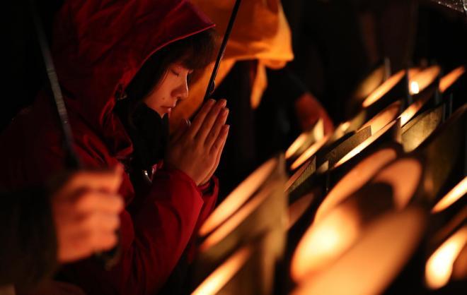 竹灯籠(どう・ろう)の火がともる中、手を合わせて祈る女性=1月17日午前5時49分、神戸市中央区、関田航撮影