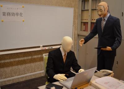 ノルマ達成と労働時間の削減を要求する上司をイメージした番組セット