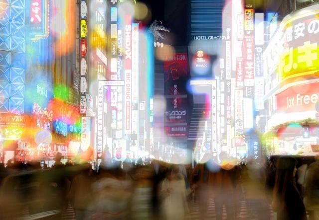 ネオンがきらめく歌舞伎町。後ろにはゴジラが顔をのぞかせる=2017年3月30日、東京都新宿区歌舞伎町1丁目