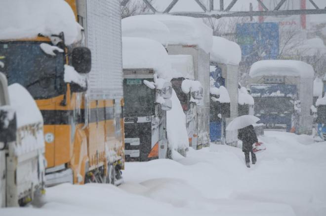 立ち往生の車列の脇を、ガソリンの携行缶を手に歩く男性=2月7日、福井県坂井市、加藤諒撮影