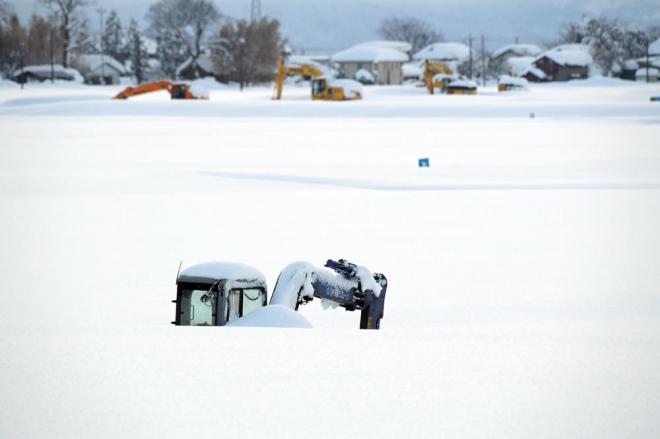 国道8号近くでは、重機が雪深く埋まっていました=2月7日午後5時1分、福井県あわら市、加藤諒撮影