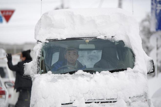 分厚い雪を載せたまま走る車=2月7日午前7時57分、福井県あわら市、加藤諒撮影