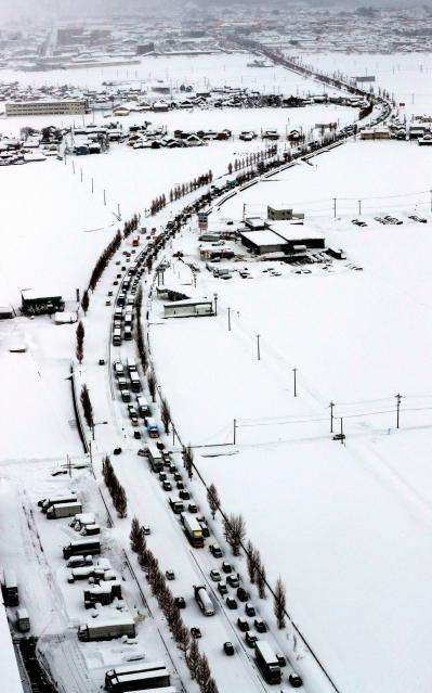 大雪の影響で国道8号では、福井市街地(写真上)へ向かう車線で大規模な渋滞が発生していた=2月6日午後2時、福井市、本社ヘリから、矢木隆晴撮影