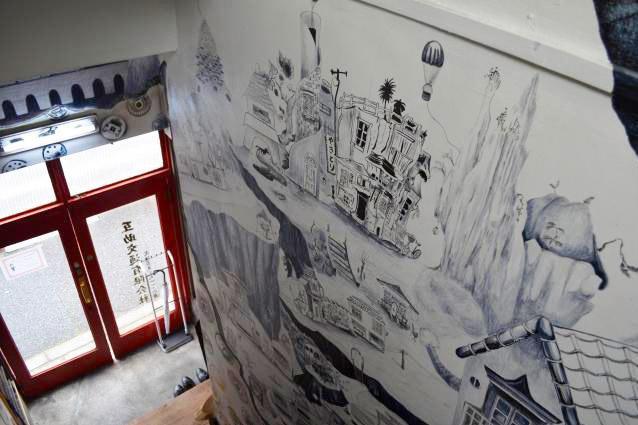 社屋の入り口すぐの階段の壁には、幻想的でノスタルジックな絵が描かれている。唯一の女性ドライバーが描いたもので、この絵を見るために訪れる人もいるのだとか。