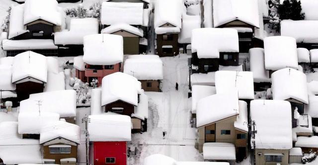 大量に積雪した民家の周辺では、住民らが除雪をしていた=2月6日午後1時51分、福井県越前市、本社ヘリから、矢木隆晴撮影