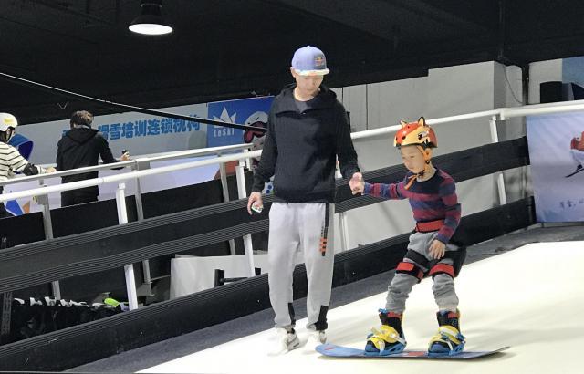 2022年北京冬季五輪の開閉会式の会場となる「鳥の巣」近くのスキー用品店では、ベルトコンベヤーのような斜面でスノーボードの練習をする人でにぎわっていた=2017年11月、北京、前田大輔撮影
