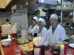 店主の上田治平さん(右)と妻のチヱ子さん(中)。家族経営で30年以上店を営んできた。