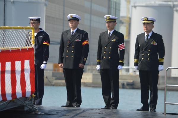 「せいりゅう」甲板で整列する乗組員。右から平間艦長と、この日の当直士官、当直海曹、当直海士。60数人が3班に分かれ6時間交代で航行にあたる=3月12日、神戸市兵庫区の三菱重工神戸造船所