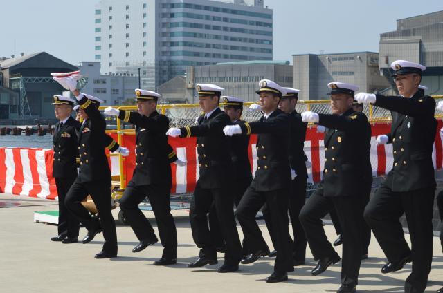 「せいりゅう」に授与された自衛艦旗を掲げ持つ副長の岡本治郎3等海佐を先頭に行進し、出港のため潜水艦へ渡る乗組員。自衛艦旗授与式で恒例の行進曲「軍艦」(軍艦マーチ)を海上自衛隊の音楽隊が演奏する=3月12日、神戸市兵庫区の三菱重工神戸造船所