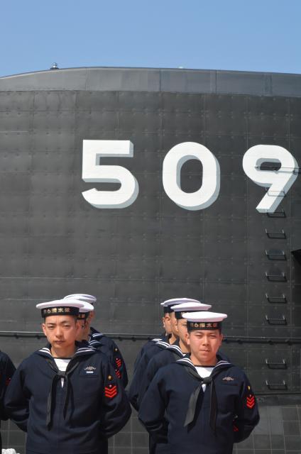 海上自衛隊の最新鋭潜水艦「せいりゅう」が配備される第二潜水隊群の「第6潜水隊」(神奈川県横須賀市)の帽子で出港の式典に臨む乗組員。せいりゅうの艦橋に書かれた艦番号「509」は出港後に消される=3月12日、神戸市兵庫区の三菱重工神戸造船所