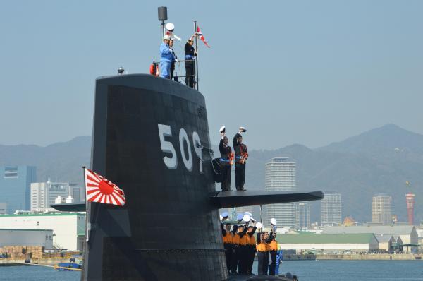 音楽隊が「蛍の光」を奏でる中、自衛艦旗を掲げ出港する「せいりゅう」艦上から帽を振る乗組員。一番上の右端が平間艦長=3月12日、神戸市兵庫区の三菱重工神戸造船所