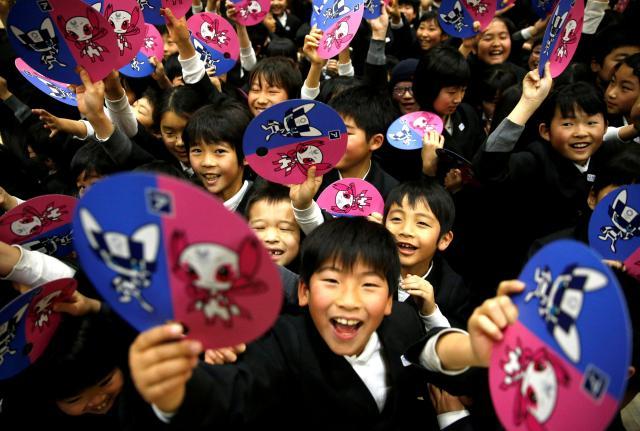 2020東京五輪のマスコットの扇を持つ小学生たち=2018年2月、東京