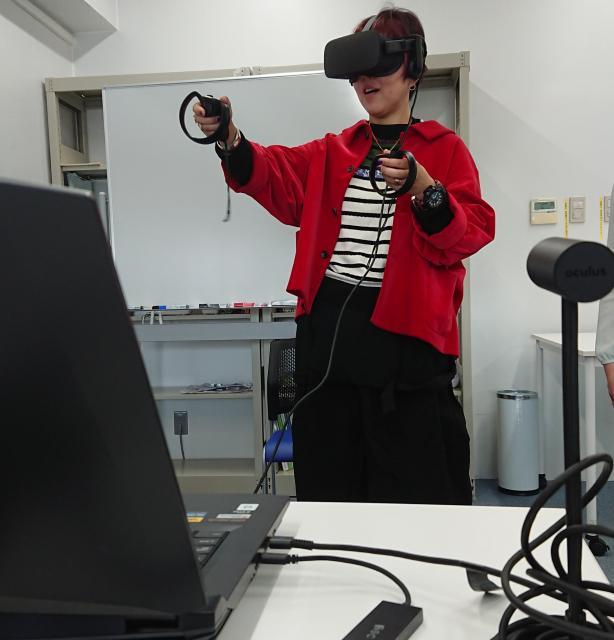 山口教授にもVRを体験してもらいました。これは、仮想空間内で物をつかんだり、ロボットとコミュニケーションをしたりといったチュートリアルアプリ