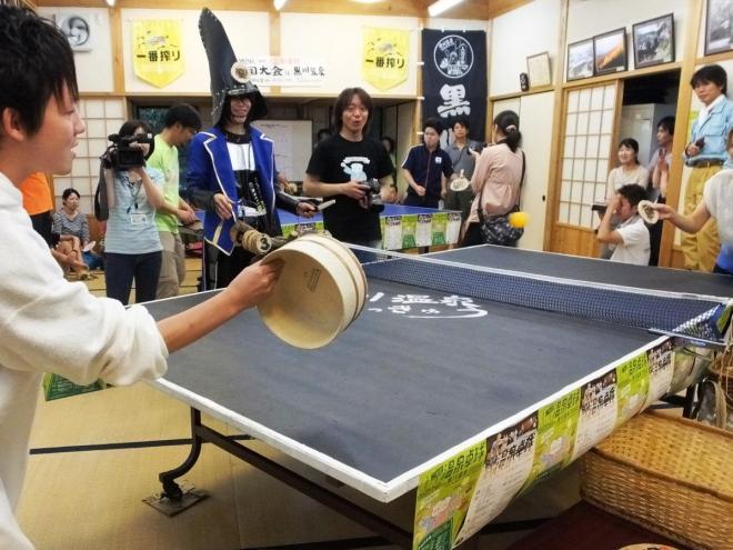 風呂おけなどを使った卓球で盛り上がる参加者=熊本県南小国町の黒川温泉