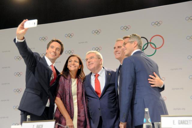 2大会同時決定を祝い、壇上で記念写真に納まる(左から)パリ招致委員会のエスタンゲ共同会長、パリのイダルゴ市長、IOCのバッハ会長、ロサンゼルスのガルセッティ市長、ロス招致委のワッサーマン委員長=2017年9月14日、遠田寛生撮影