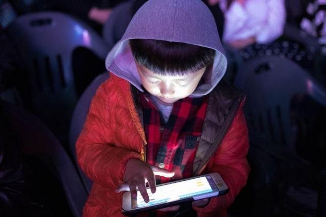 「eスポーツ」世界大会の会場で、自分用のタブレット端末でオンラインゲームを楽しむ少年=2017年9月29日、ソウル市庁前広場、野上英文撮影