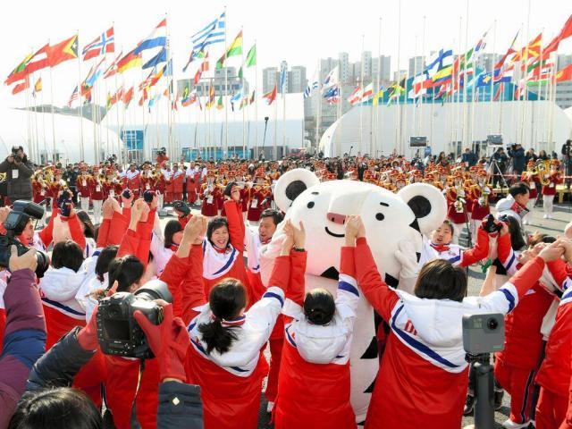 入村式で手をつないでマスコットキャラクターと踊る北朝鮮の選手団=2018年2月8日、韓国・江陵、白井伸洋撮影