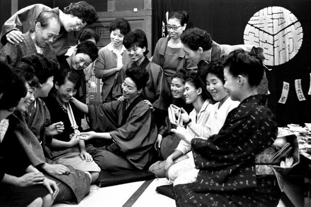 1964年の東京五輪の後、宿泊先の旅館で、従業員たちにバレーボールの金メダルを見せる選手たち。「東洋の魔女」と呼ばれ一番ブームを巻き起こした=1964年11月6日
