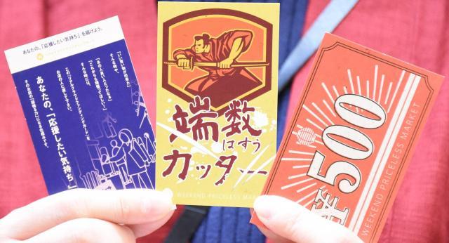 来場者に配られる「リアルクラウドファンディングカード」(左)など=2018年3月4日