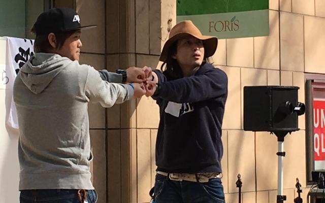 街頭ライブで四つ葉のクローバーを手でつくるLAWBLOWの2人=2018年3月11日、東京都府中市