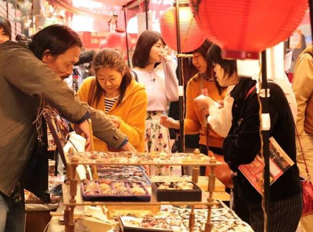 お店の人(左)から、商品が出来るまでの過程や特徴などを聞きながら品定めするお客さんたち=2018年3月4日