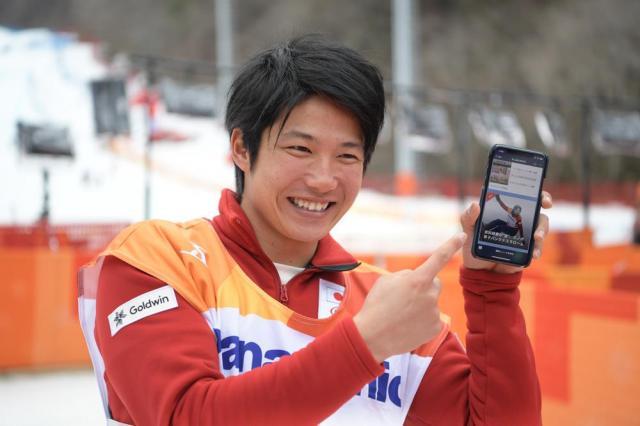 バンクドスラロームで金メダルを獲得し、LINEニュースの速報に掲載された写真を見せて笑顔の成田緑夢選手