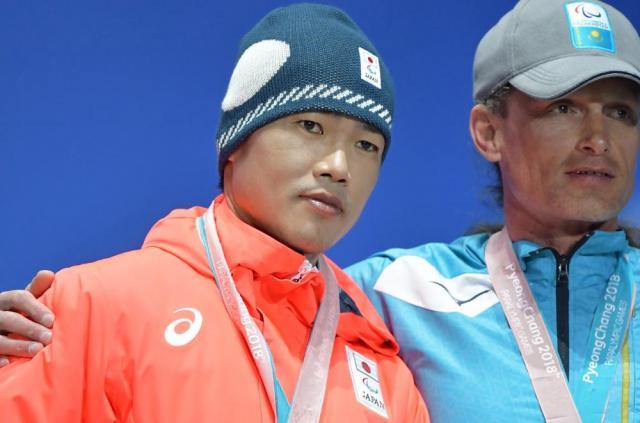 スキー距離男子スプリント・クラシカル立位の表彰式で、銀メダルを胸に撮影に応じる新田佳浩選手。