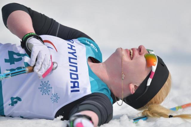 スキー距離スプリントでゴールして倒れ込む選手