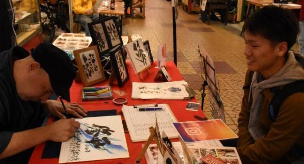 福岡から卒業旅行で訪れたという高校生(右)の名前を書にしたためる書家。完成後、「さあ、いくら?」=2018年3月4日