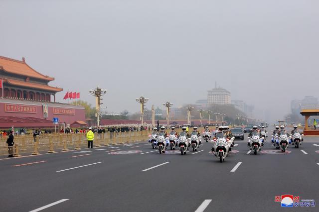 天安門広場の前を横切る車列。21台のバイクが先導したという。朝鮮中央通信配信