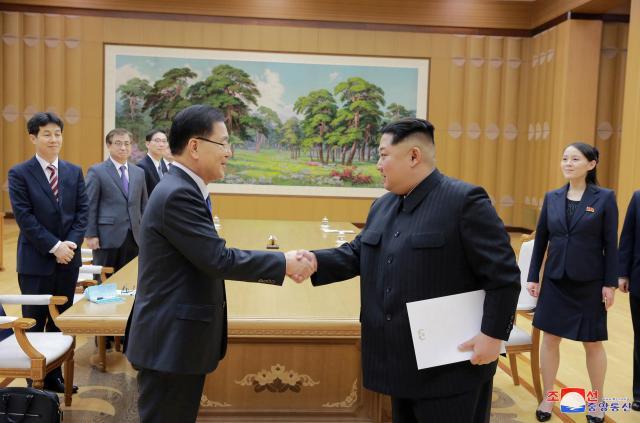 韓国大統領府の鄭義溶・国家安保室長(左)と平壌で3月5日に会い、握手する北朝鮮の金正恩・朝鮮労働党委員長。朝鮮中央通信が6日に配信した。ソウルに戻った鄭氏は6日に「4月末の南北首脳会談開催」を発表し、8日にホワイトハウスを訪問。金氏が会談を望んでいると鄭氏から聞いたトランプ米大統領は、5月までにと応じた。