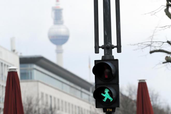 「アンペルマン」の信号機。後ろに見えるのは旧東ベルリン側にあるテレビ塔=石合力撮影