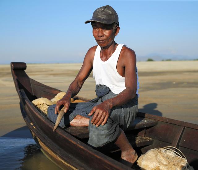 漁の最中、小舟のヘリに座り、木でたたいて音を出すマウンレイさん。視線はじっと水面を見つめていました=2017年12月、ミャンマー中部
