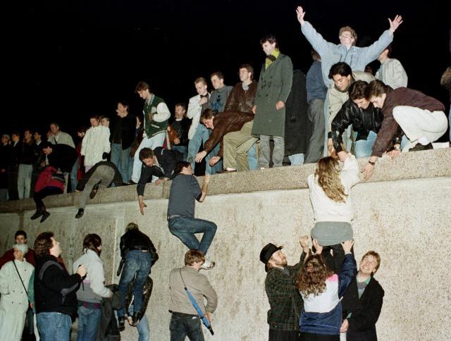 ベルリンの壁をよじ登る東ドイツの市民たち=1989年11月10日