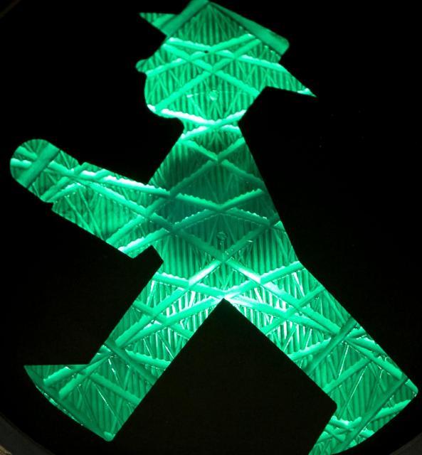 アンペルマンの青信号。今にも歩き出しそうにつま先をあげている